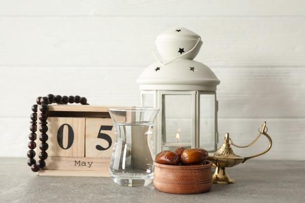 Украшение и еда с календарем на сером столе на деревянном фоне