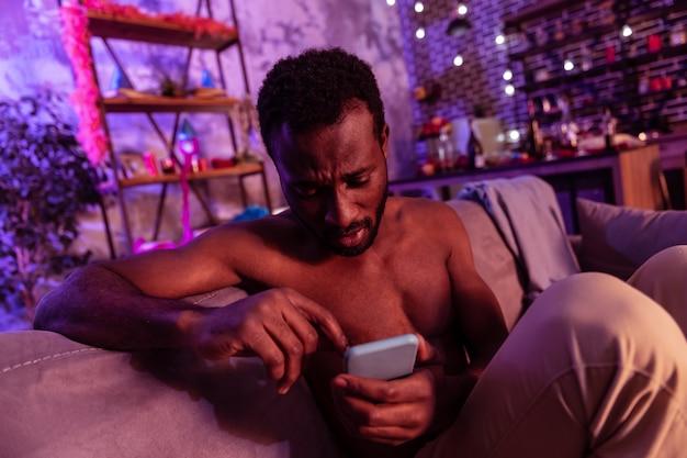 장식과 쓰레기. 알코올 중독 후 기분이 좋지 않은 동안 소셜 미디어를 확인하는 단발 머리 남자 동정