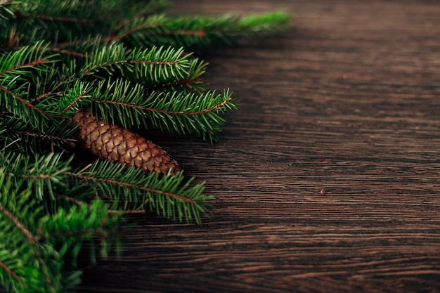 Decoration of christmas tree green branches on a brown background with copyspace