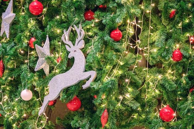 사슴 장난감, 빨간 공, 별, 축하용 전구가 있는 장식 크리스마스 트리