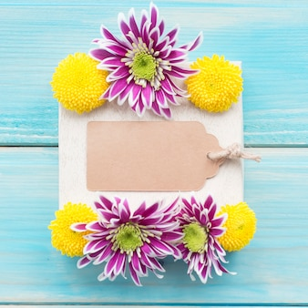 Decoration of chrysanthemum flowers with blank tag on wooden table