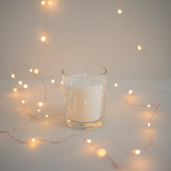 Decoration of fairy lights around glass candleholder