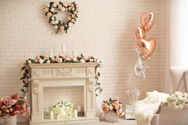 Decoration of the fireplace with flowers in a bright interior festive decoration with helium, balloons