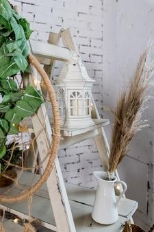 콘크리트 벽에 마른 허브, 램프, 양 초 및 화로 만든 아늑한 집 장식 건조 한 꽃과 현대적인 인테리어에 식물. 에코 스타일의 인테리어 장식