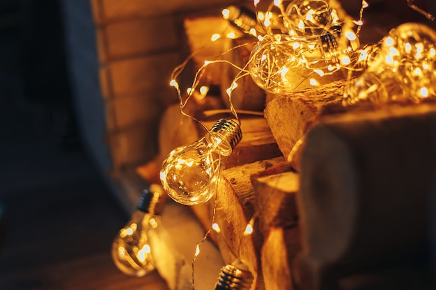 Decoration gerland christmas lights bulb lying in fireplace on wooden firewood loft design
