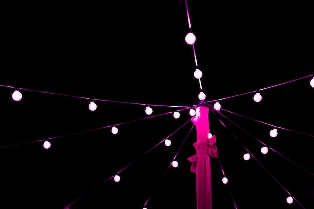 Decoration of glowing pink string light bulb at night