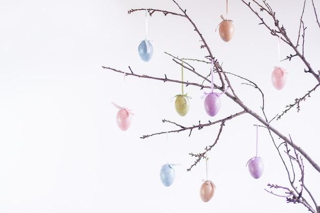 Украшение в виде пасхальных яиц на ветвях деревьев на белом фоне. пасхальный фон.
