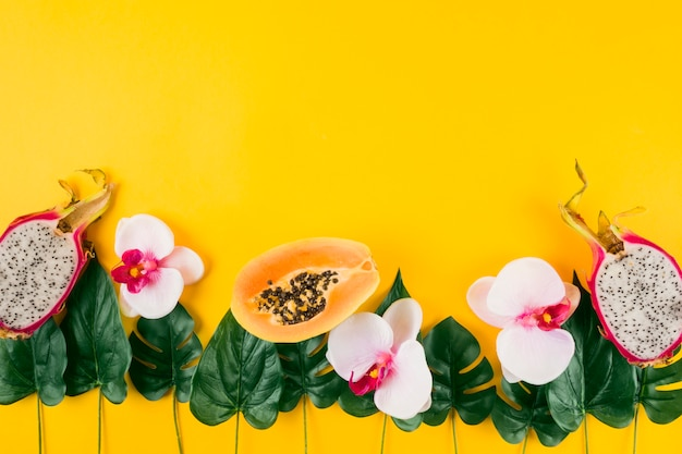 Decoration made with papaya; dragon fruits; orchid and artificial leaves on yellow background