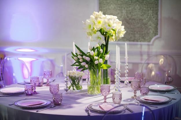 레스토랑 내부의 웨딩 테이블에 백합과 튤립 꽃으로 축제 저녁을 장식합니다. 보라색 톤으로 축하를 위해 테이블을 장식했습니다.