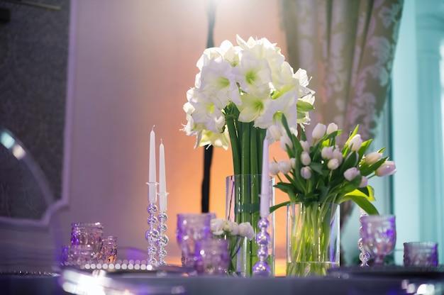 レストランのインテリアの結婚式のテーブルにユリの花でお祝いディナーの装飾。結婚式の装飾。