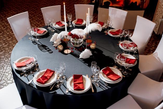 燃えるろうそくでテーブルの装飾、黒、赤、白の色合いの装飾