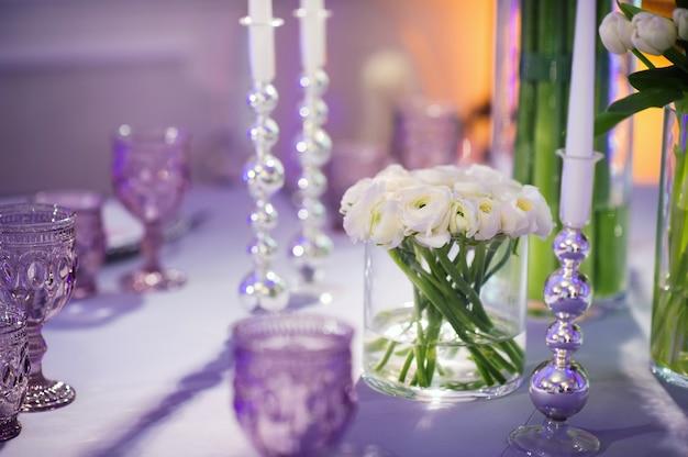 レストランのインテリアの結婚式のテーブルに花で夜のお祝いディナーの装飾。結婚式の装飾。