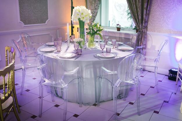 레스토랑 내부의 웨딩 테이블에 백합과 튤립 꽃으로 축제 저녁 장식. 축하 테이블 장식.