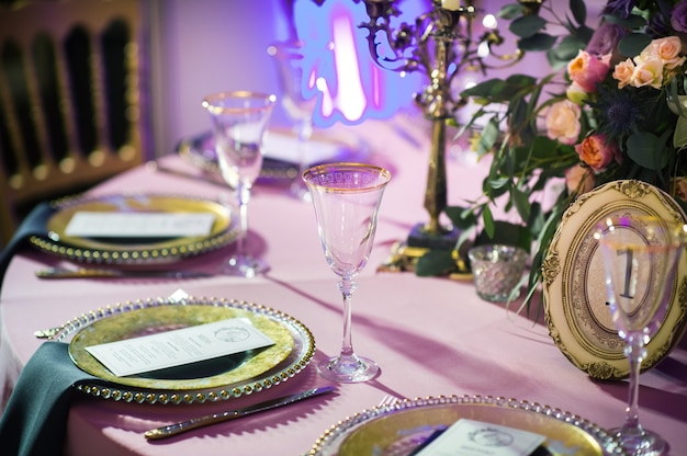 레스토랑 내부의 웨딩 테이블에 장미 꽃으로 축제 저녁 장식. 축하 테이블 장식.