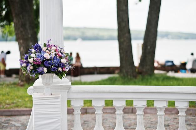 紫と紫の花を持つ結婚式のアーチの装飾