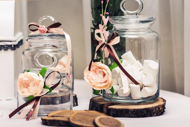 お祝いのテーブルの装飾:瓶の中のマシュマロ、木の円形断面、花。