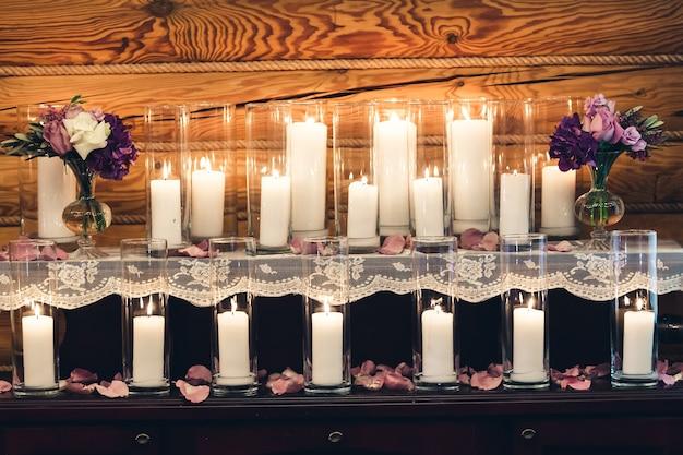テーブルの装飾:グラスのキャンドル、花瓶の紫色の花。