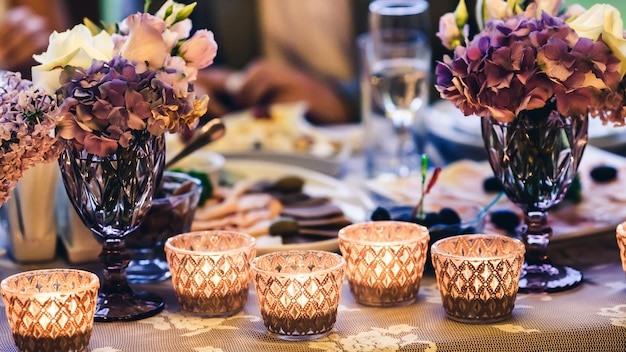 グラスのテーブルキャンドルの装飾、花瓶の紫色の花