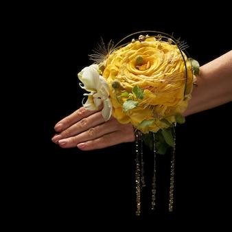 大きな黄色い花の形で花嫁の手首に装飾