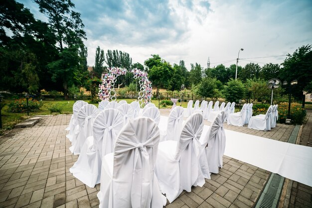 Decoration of an outdoor ceremony in a green garden, an arch of fresh flowers, a white path for newlyweds, chairs in white fabric covers