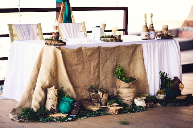 Decoration of wedding table in rustic style with burlap, stumps, candles, greenery.