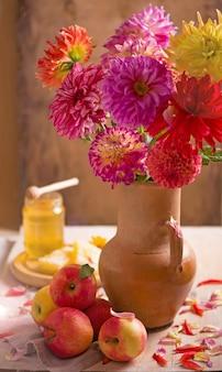 テラコッタの植木鉢に黄色とオレンジ色のダリアの花で飾られています。
