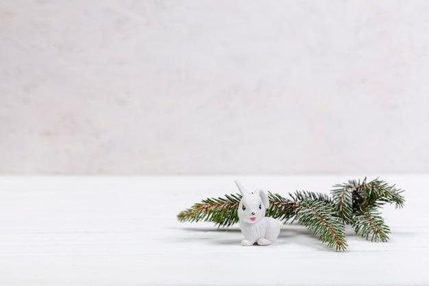 Украшение веткой ели и белым кроликом