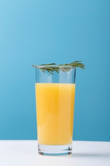 Decoration with glass of orange juice and herbs