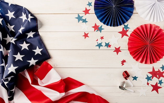 Decorations for 4th july, independence day usa. paper fans, national flag, stars and noisemakers on white wooden background. copy space, flat lay