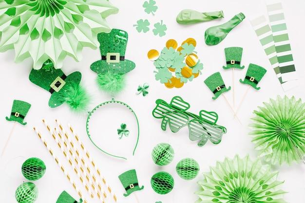Декорации и реквизит для празднования дня святого патрика. зеленые и золотые бумажные украшения, обруч для волос со шляпами, лист клевера, солнцезащитные очки, воздушные шары, конфетти и конфеты на белом фоне. плоская планировка, вид сверху
