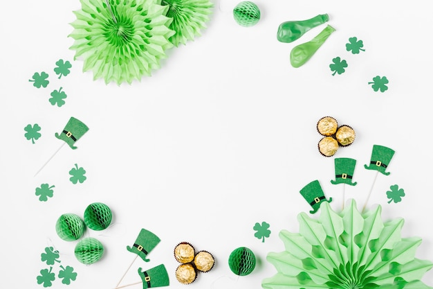 Декорации и реквизит для празднования дня святого патрика. зеленые и золотые бумажные украшения, шляпа, воздушные шары, конфетти, конфеты и счастливые символы на белом фоне. праздничная концепция. плоская планировка, вид сверху.