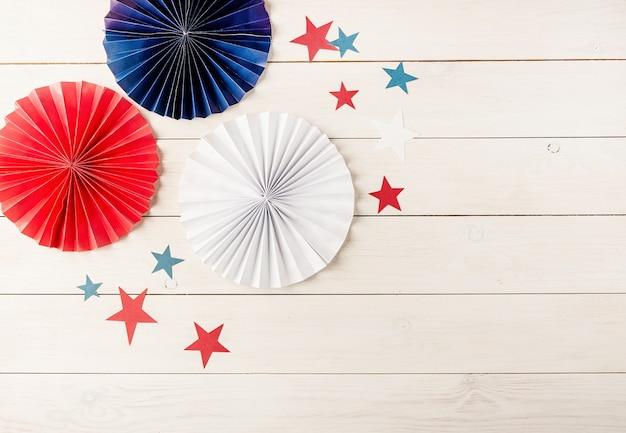 7 月 4 日のアメリカ独立記念日の装飾。うちわと白い木製の背景の星。コピー スペース、フラット レイアウト