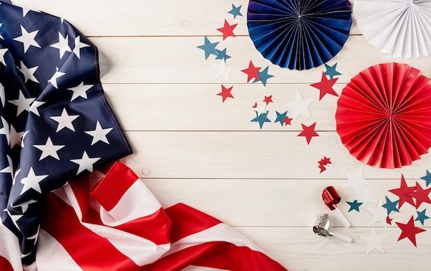 7 月 4 日のアメリカ独立記念日の装飾。紙の扇子、国旗、星、白い木の背景に騒音を発生させる人。コピー スペース、フラット レイアウト