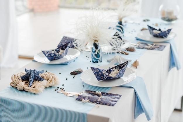 Украшения для сервировки праздничного стола. морской стиль. элегантные тарелки, бумажные стаканчики, синий текстиль. бумажные кораблики со сладостями. день рождения или концепция детского душа мальчика.