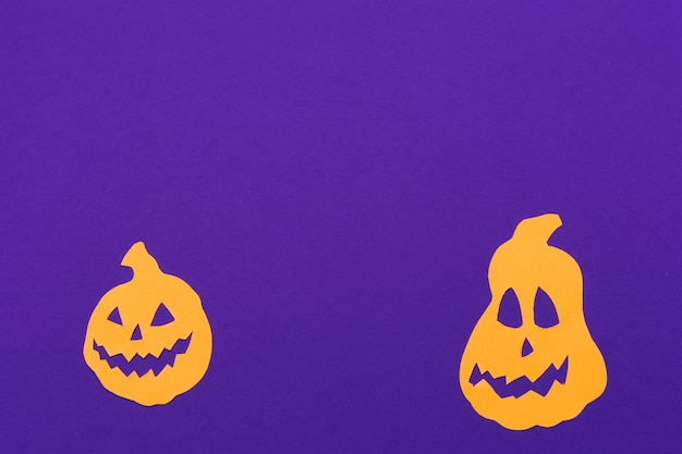 Decorations for halloween party. pumpkins on purple background