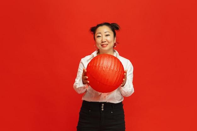 Decorazioni per l'umore. . lanterna asiatica della tenuta della giovane donna sulla parete rossa in vestiti tradizionali. sorridendo, sembra felice. celebrazione, emozioni umane, vacanze. copyspace.