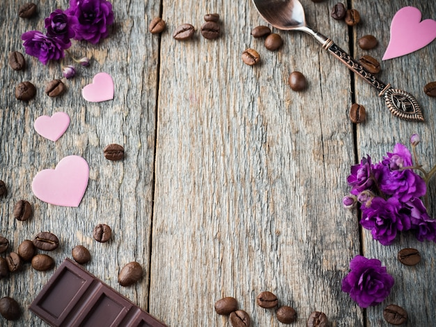 Decorations for valentines day paper hearts, violets and chocolate coffee on rustic wooden background.