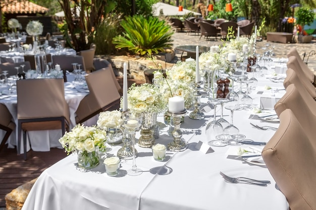 Decorations of the wedding table with flowers and dishes.