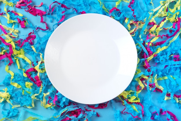 Decorative abstract background of colored paper on a blue background white plate on blue background
