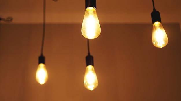 黄色の壁の背景に装飾的なアンティークエジソンスタイルのライトタングステン電球