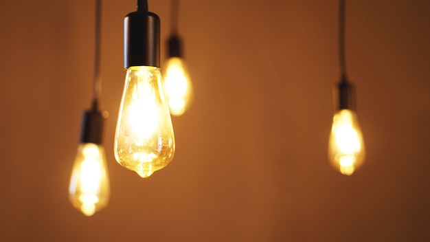 Decorative antique edison style light tungsten bulbs against yellow wall background