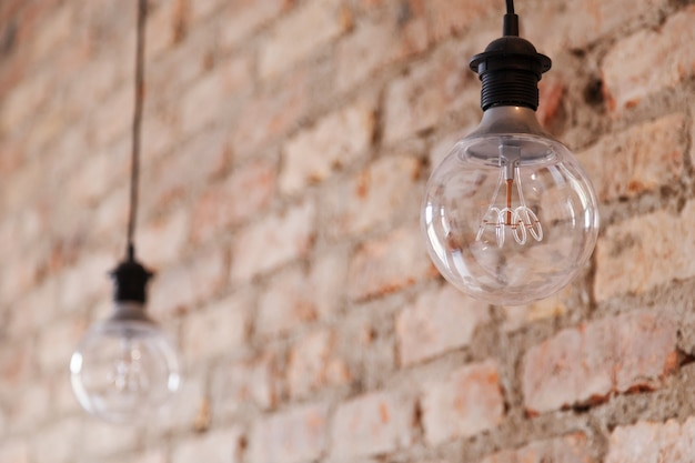 Decorative antique style light bulbs against brick wall background