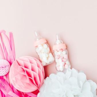 ベビーシャワーパーティーのためのキャンディーと紙の装飾が施された装飾的なベビーミルクボトル。フラットレイ、上面図