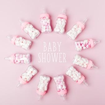 キャンディー付きの装飾的なベビーミルクボトル。ベビーシャワーパーティーの装飾。フラットレイ、上面図
