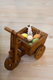 Декоративная корзина в виде мотоцикла, в которой пасхальные яйца с зайчиком.