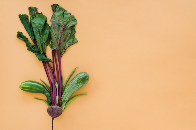 Decorative beetroot with leaves; green beans; cucumber and zucchini on brown backdrop