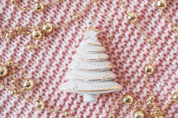 装飾的なベージュのクリスマスツリーとピンクのニットの背景に金の花輪。新年またはクリスマスカード
