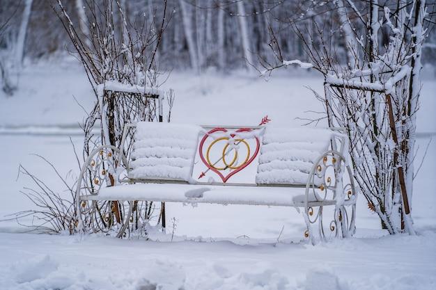 겨울 도시 공원에서 마음으로 장식 벤치는 눈으로 덮여 있습니다. 겨울철 연인을위한 벤치, 클로즈업