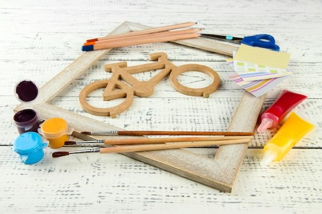 木製のテーブルに針細工の構成を持つ装飾自転車