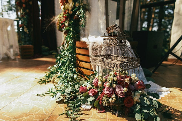 Decorative bird cage full of red roses, spearworts and greenery